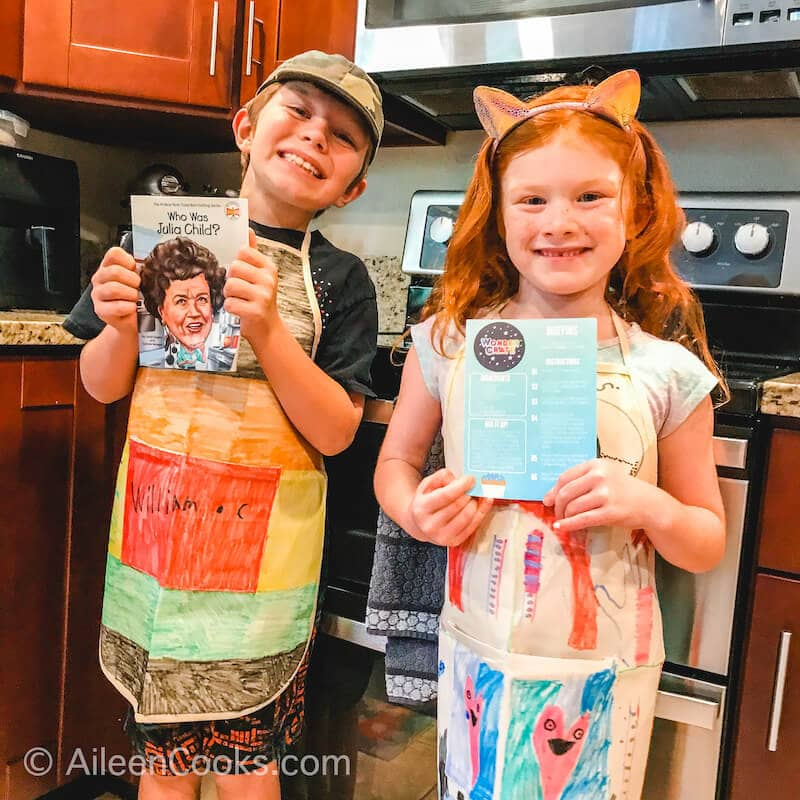 Two kids in colorful aprons smiling and standing in a kitchen.