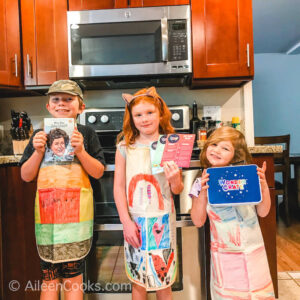 Three kids standing in colorful aprons and standing in a kitchen.