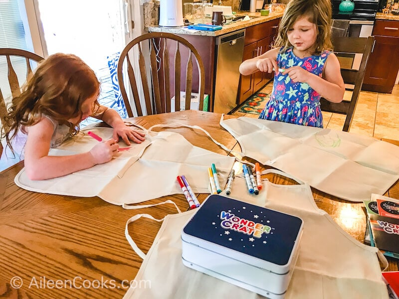 Two girls sitting at a wooden table, decorating aprons with fabric markers.