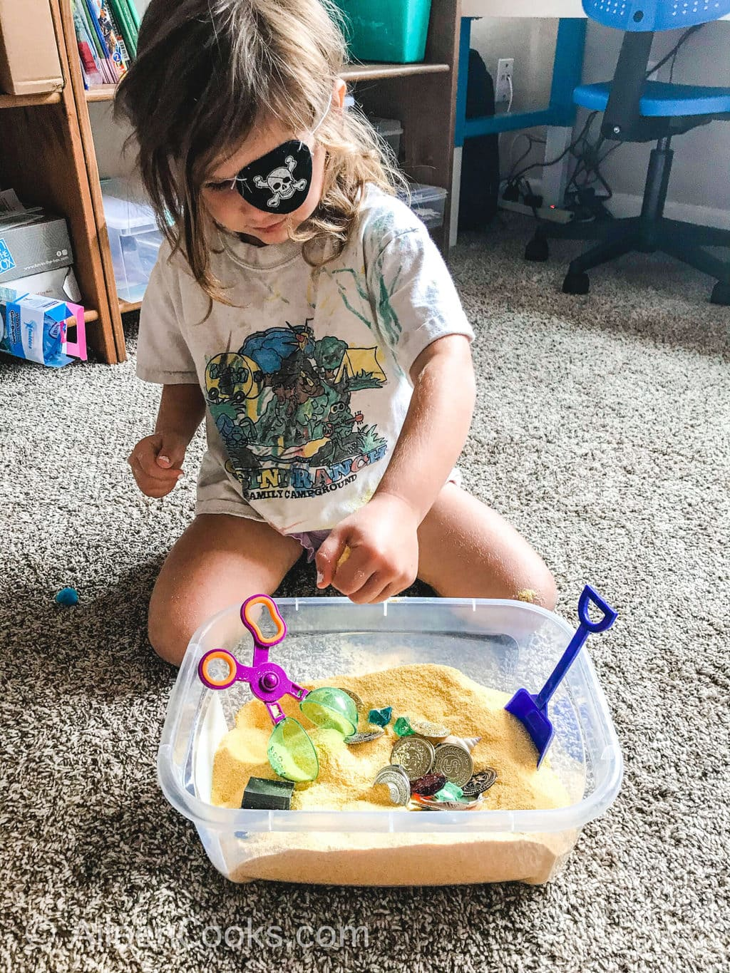 A little girl playing with a pirate themed sensory box and wearing a pirate eye patch.