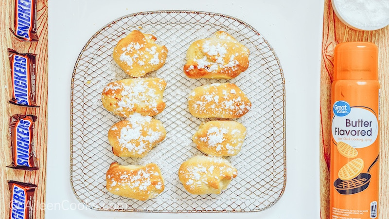 8 air fryer snickers on an air fryer tray and dusted with powdered sugar.