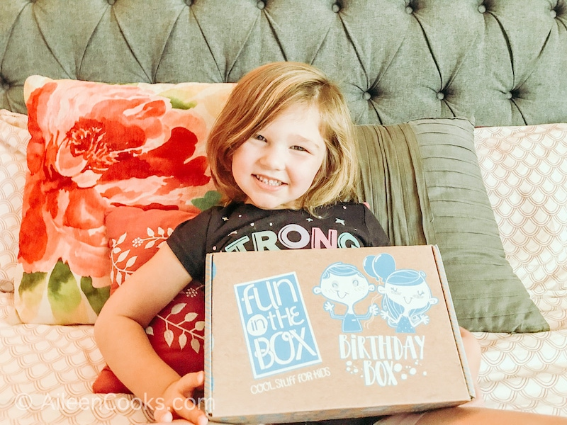 A girl holding a Fun in the Box Birthday Box.
