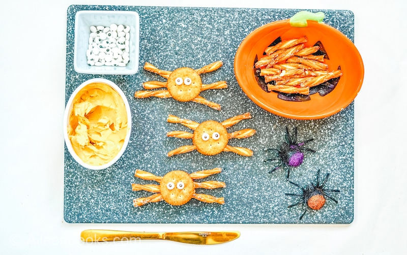 Spider decorated crackers with candy eyes, on a grey cutting board.