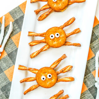 Halloween spider crackers on a white platter next to two fake skeleton arms.