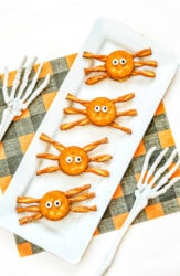A white platter of four cracker sandwiches decorated as spiders.