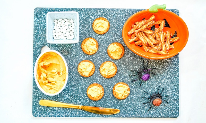 Pumpkin spice cream cheese spread on seven crackers.