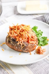 A baked potato on a white plate and topped with shredded chicken and cheese.