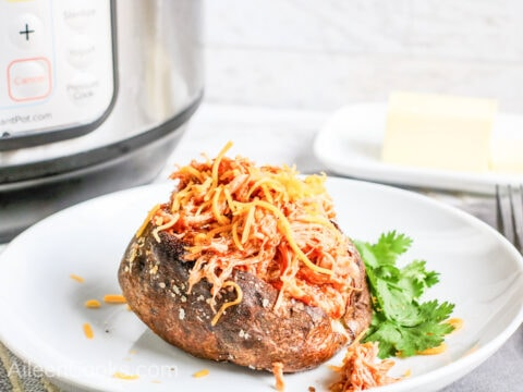 Side view of baked potato loaded with barbecue chicken in front of instant pot.