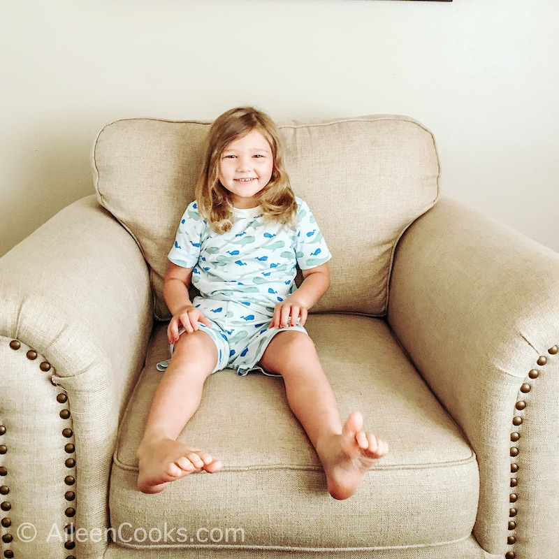 A little girl sitting on a beige upholstered chair, wearing shark Peejamas.