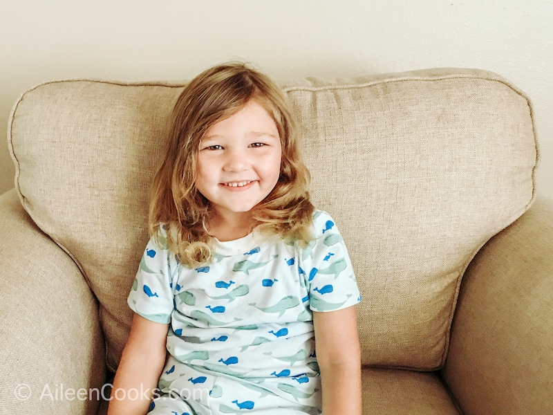 A little girl smiling, wearing light blue shark pajamas.