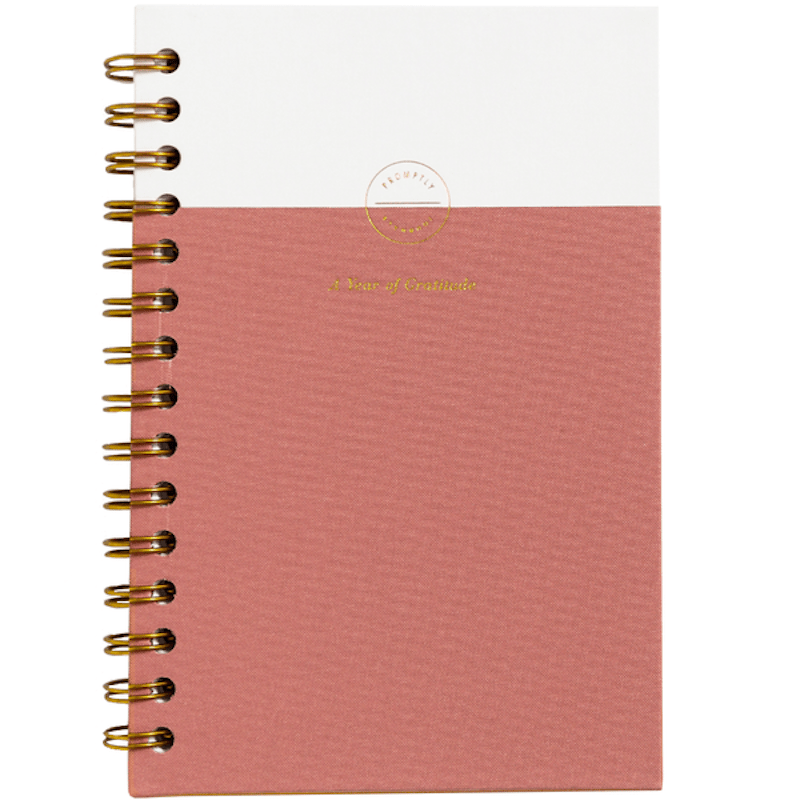 A rose colored journal with a white stripe on top.