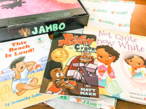 "Three children's book sitting next to a black box that says ""Jambo"" in green lettering."