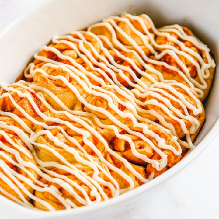 Pumpkin cinnamon rolls in a baking dish with frosting on top