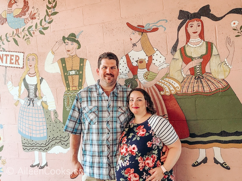 A man and woman standing in front of the mural at Hofas House Hotel.