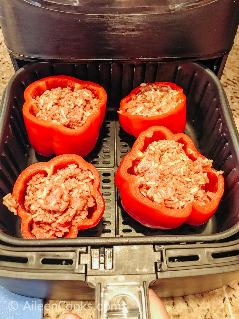 Stuffed bell peppers inside of air fryer.