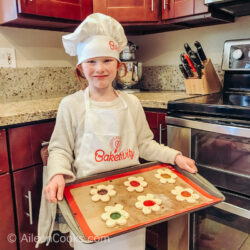 A girl in an apron and chef hat, holding a cookie sheet of baked cookies.