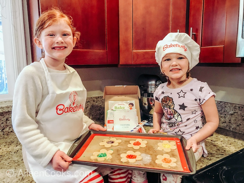 Two girls sitting on a counter holding a cookie sheet of flower-shaped cookies with candy centers.