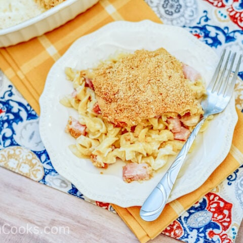 A plate of chicken cordon bleu casserole on a blue and yellow placemat.