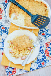 A white casserole dish next to a white plate filled with a large portion of chicken cordon bleu casserole.