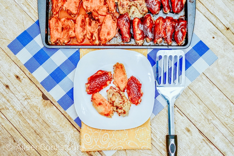 A sheet pan with baked chicken wings with three different sauces on them.