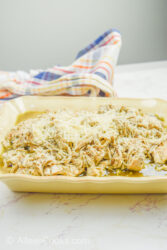 Side view of pesto chicken in a beige serving dish.