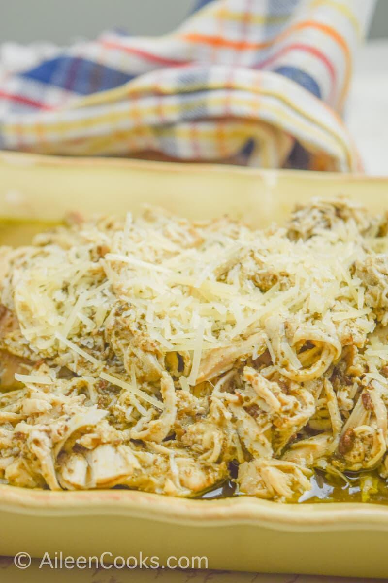 Close up of crockpot pesto chicken in a beige serving dish.