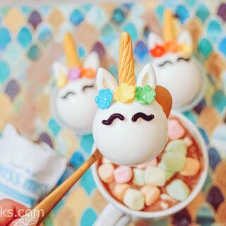 A gold spoon holding a unicorn hot cocoa bomb over a white mug of hot cocoa.
