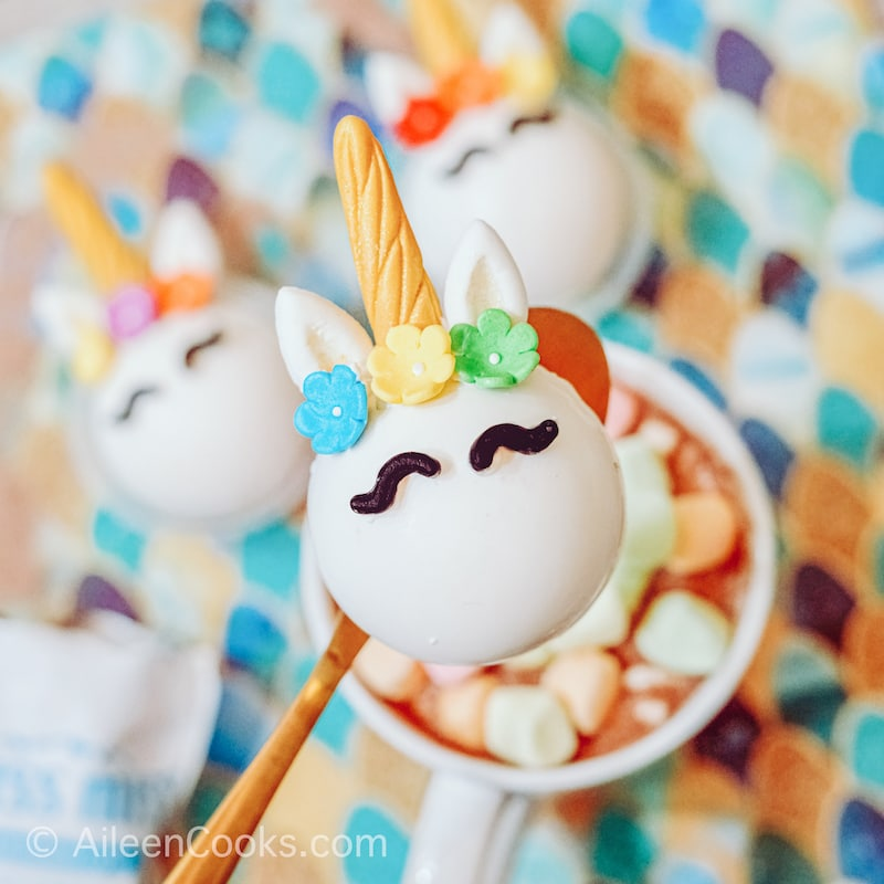 A gold spoon holding a unicorn cocoa bomb over a mug of hot cocoa with rainbow marshmallows.