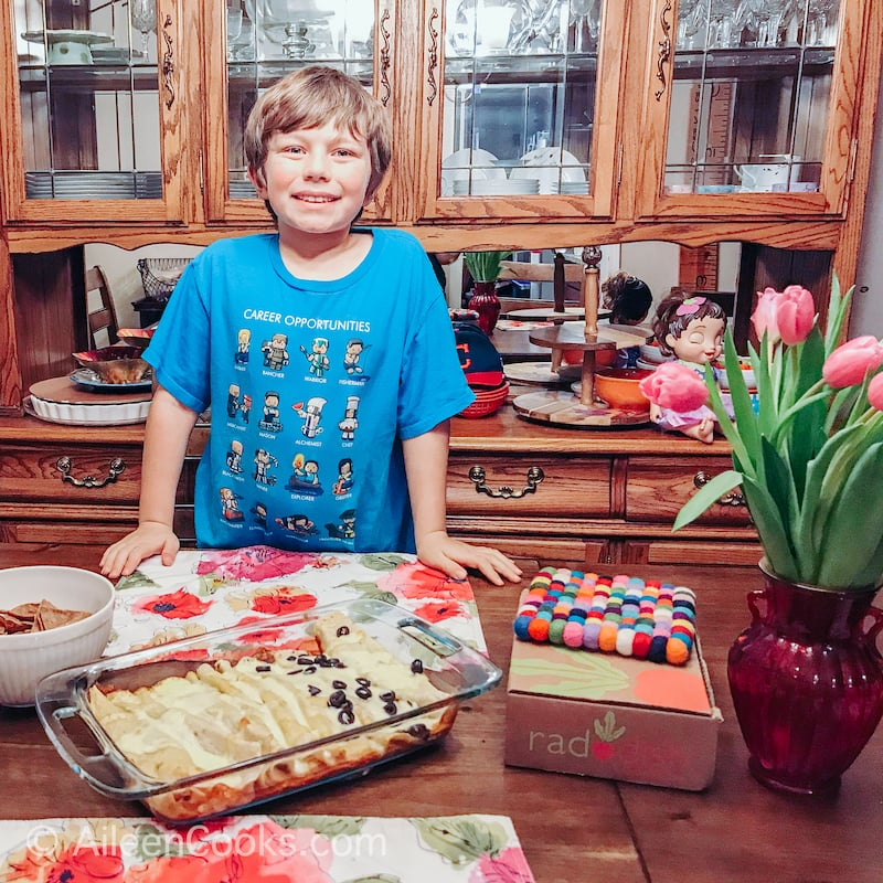 A boy in a blue shirt, standing in front of a dish of enchiladas.