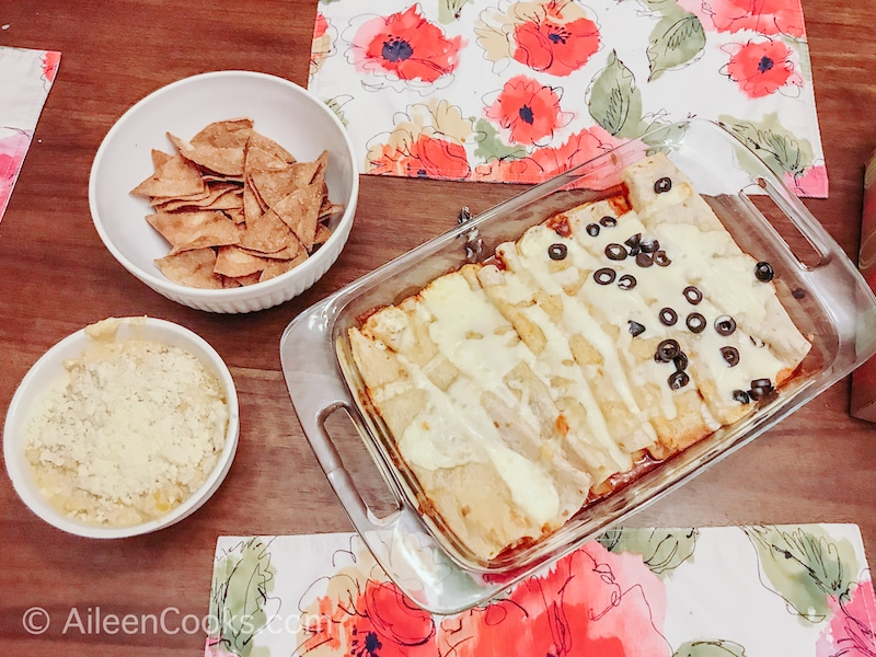 Overhead shot of enchiladas, corn dip, and homemade tortilla chips on a wooden table.