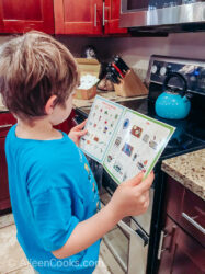 A boy in a blue shirt reading a recipe card.