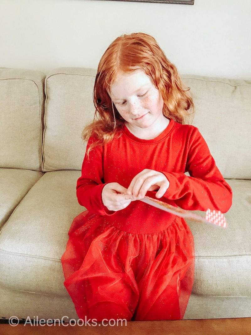 A little girl sitting on a couch, opening a yellow envelope.