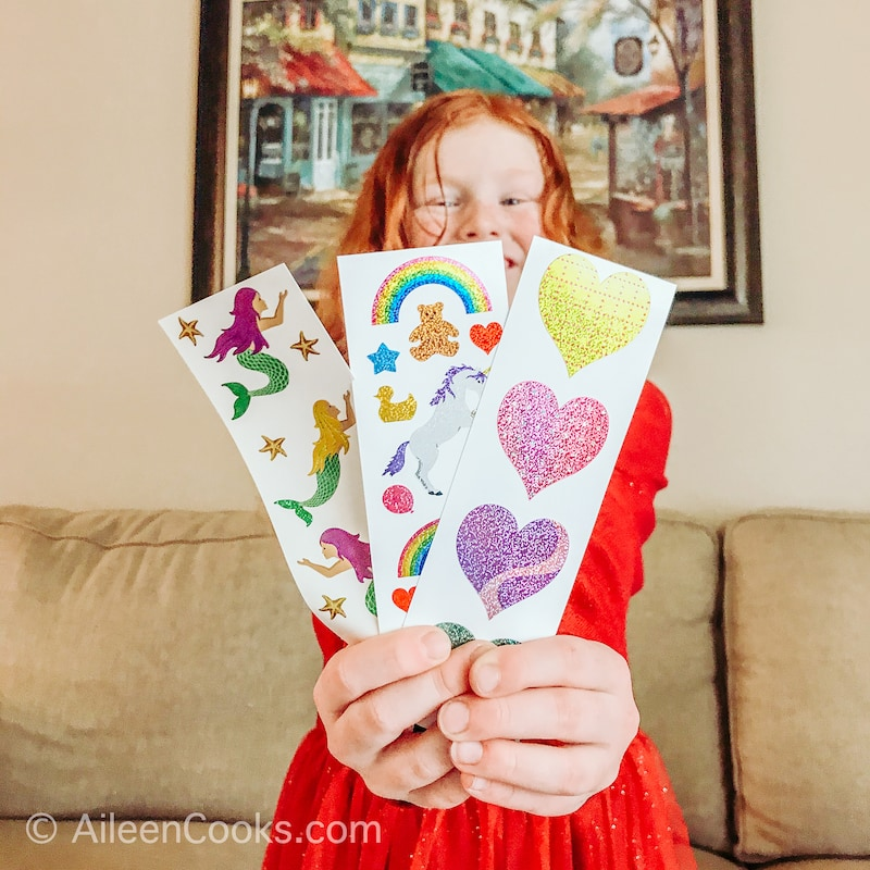 A little girl holding up three sheets of stickers.