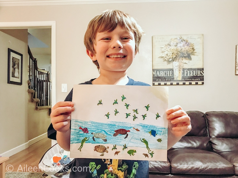 A boy holding up a picture decorated with stickers.