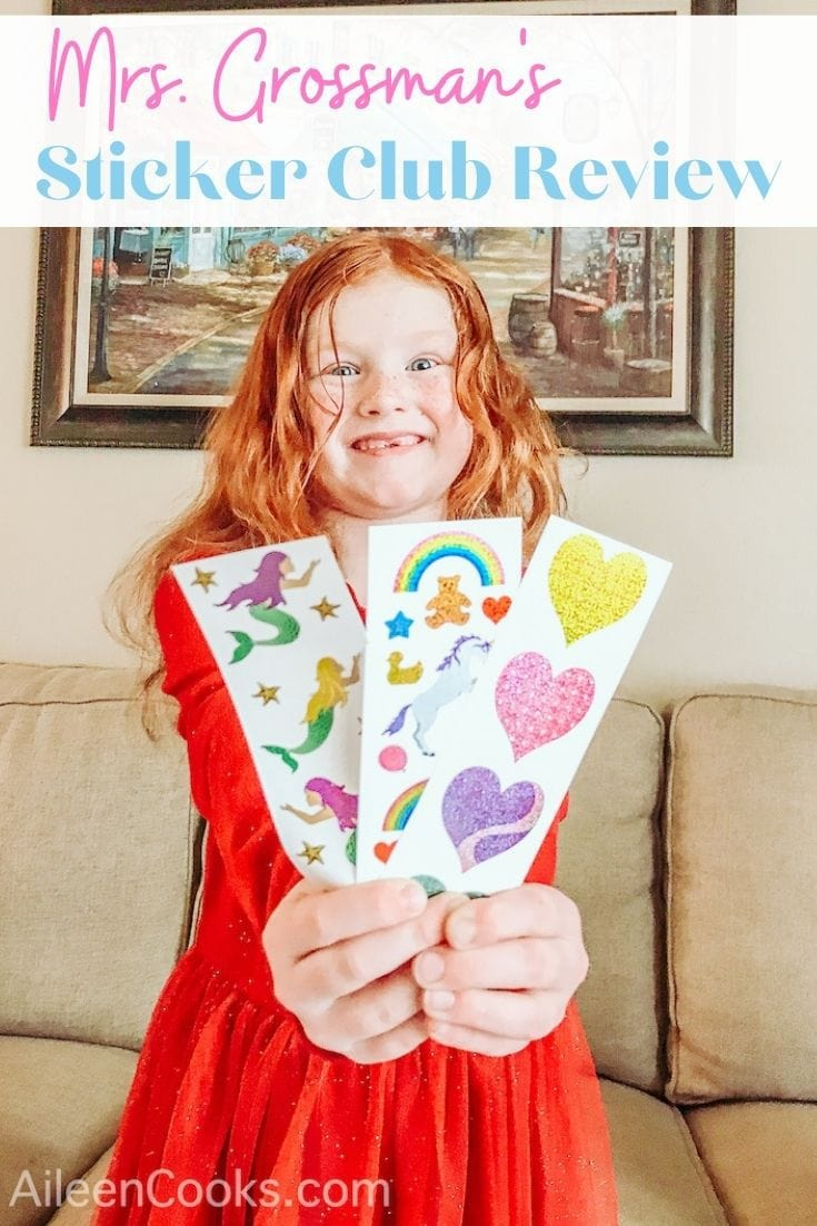 """A little girl holding up three sheets of stickers with the words """"Mrs. Grossman's Sticker Club Review"""" in pink and blue lettering."""