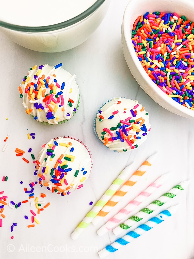 Three white hot cocoa bombs covered in rainbow sprinkles.