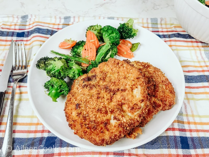 A white plate of crispy air fryer pork chops and mixed vegetables.
