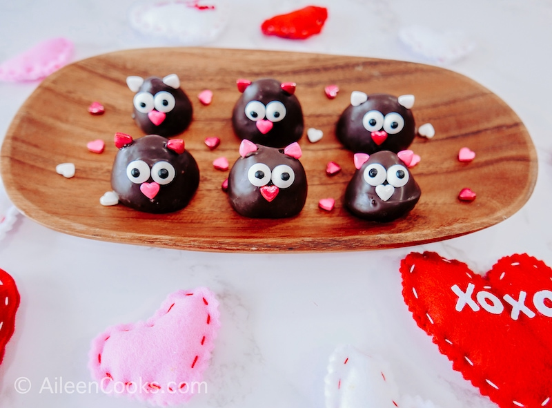 6 chocolate covered strawberry love birds on a wooden tray.
