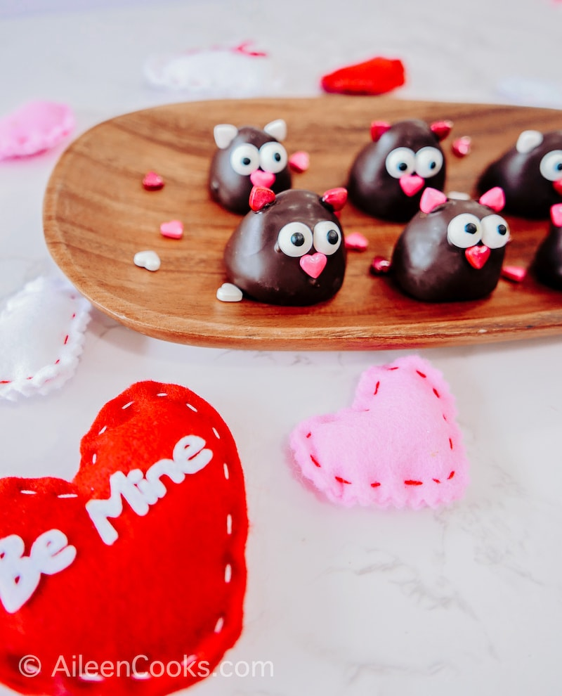 """A red heart with the words """"be mine"""" in front of a tray of chocolate covered strawberries."""