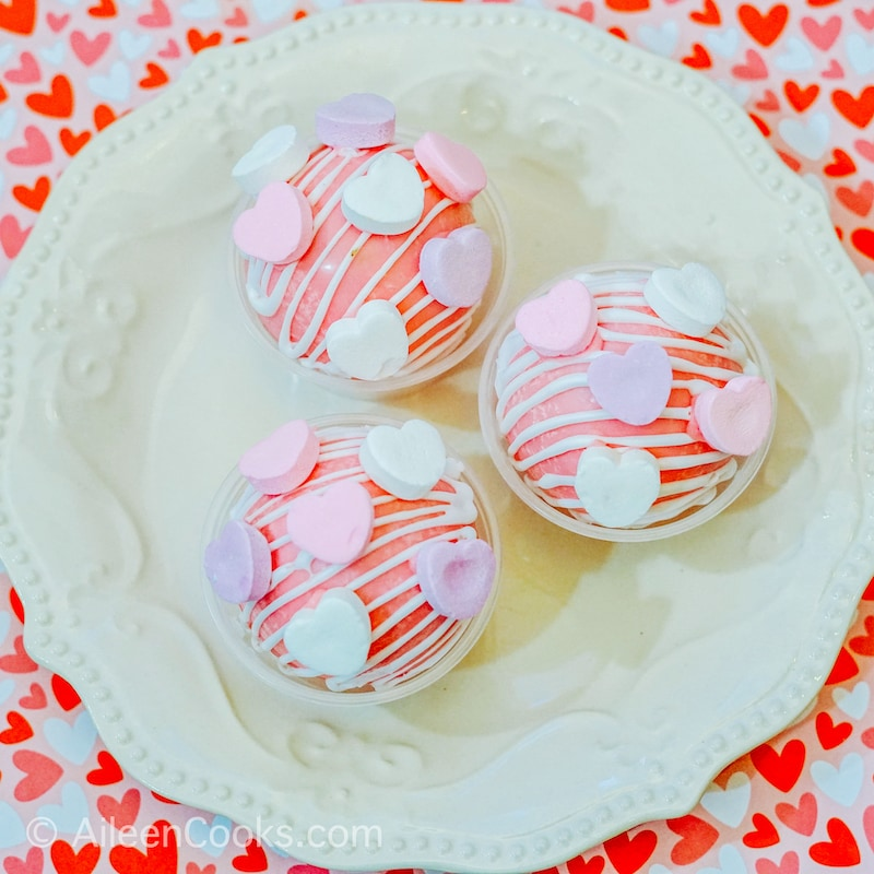 Close up of three Valentine's Day hot chocolate bombs on a white plate.