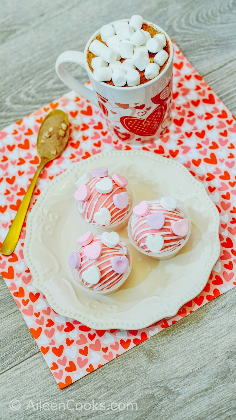 Three hot cocoa bombs on a white plate, on top of a Valentine's Day placemat.