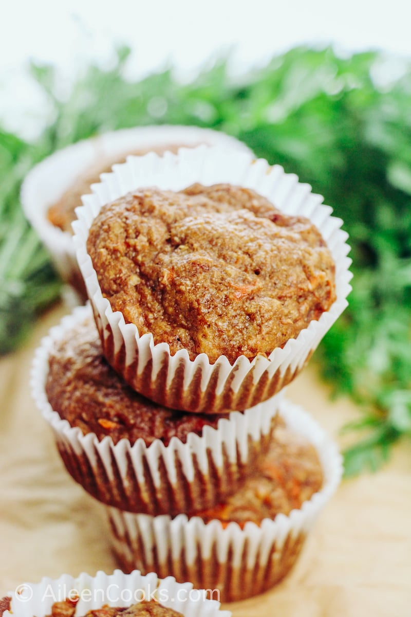 An arrangement of six carrot muffins in white paper muffin cups.