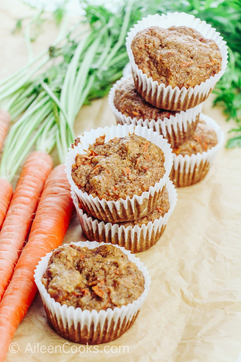 A large bunch of carrots next to stacked up carrot muffins.