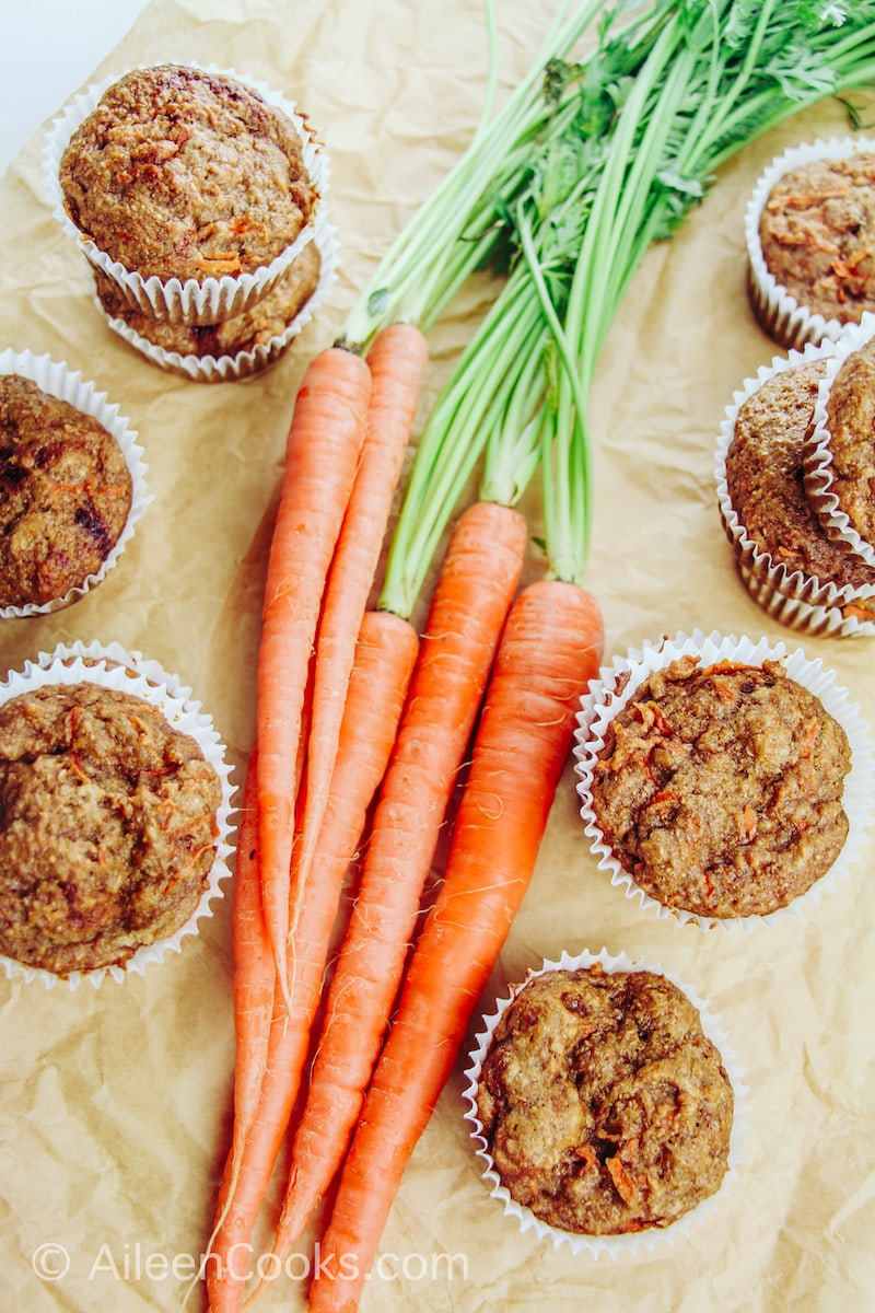 A bunch of carrots surrounded by healthy carrot muffins.