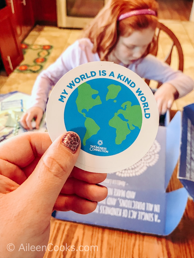 A hand holding up a sticker of Earth.