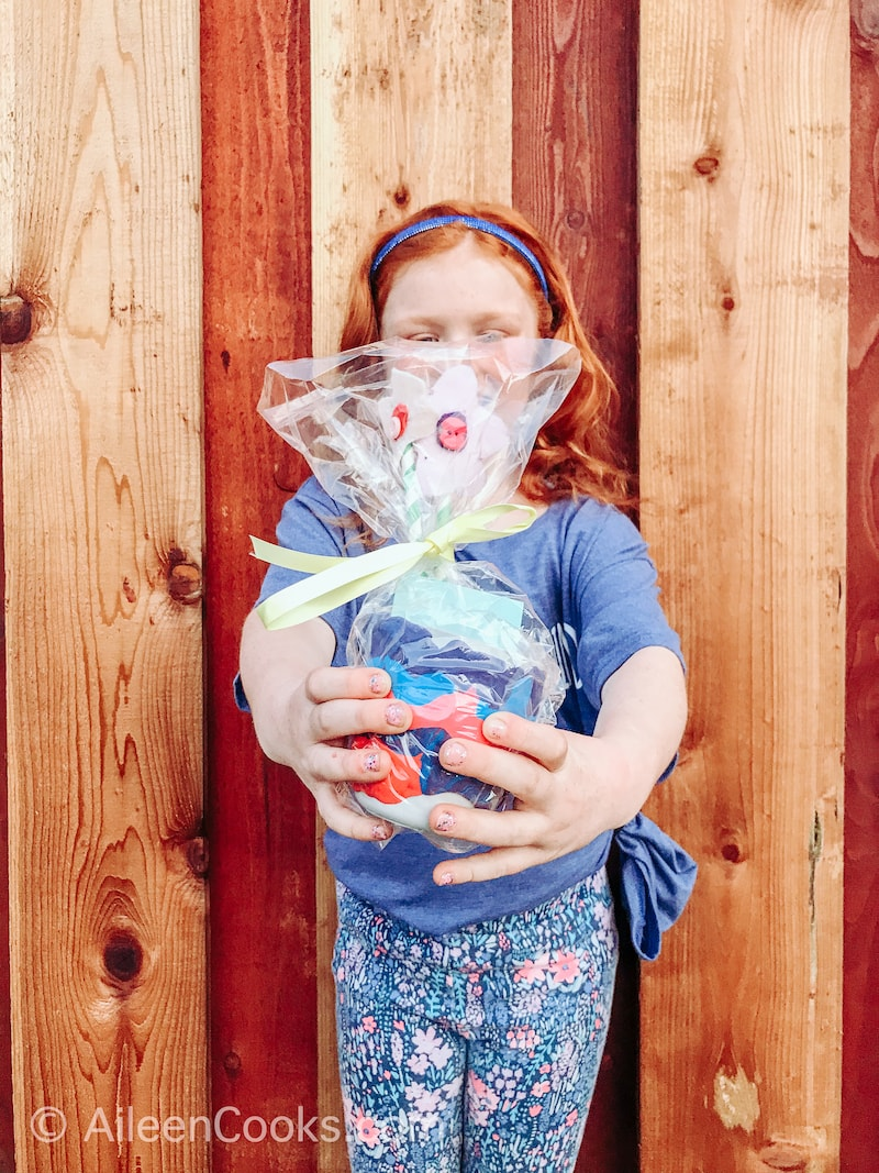 A red-haired girl holding out a homemade vase wrapped in plastic.