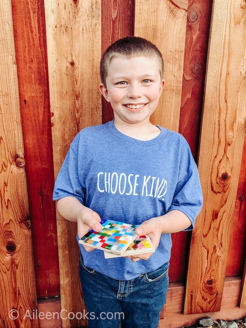 A boy smiling and holding two hand-made mosaic coasters.