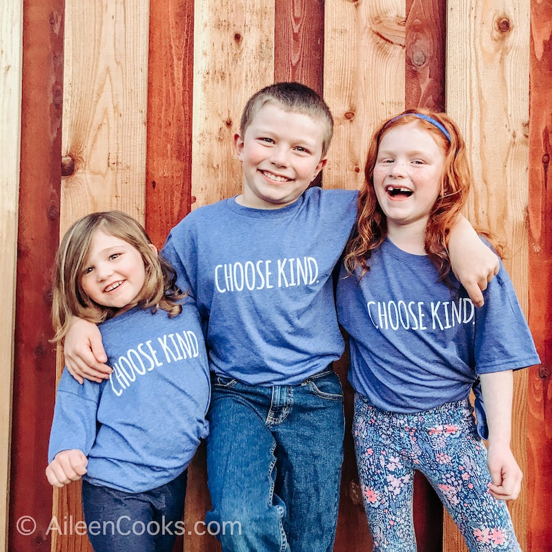 Three kids standing in front of a wooden fence,