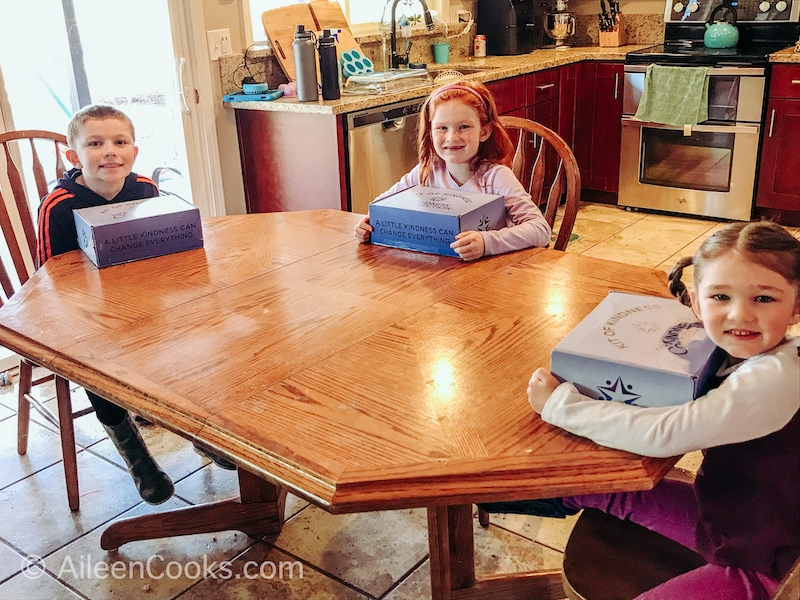 Three kids sitting at a table with kindness kit boxes.