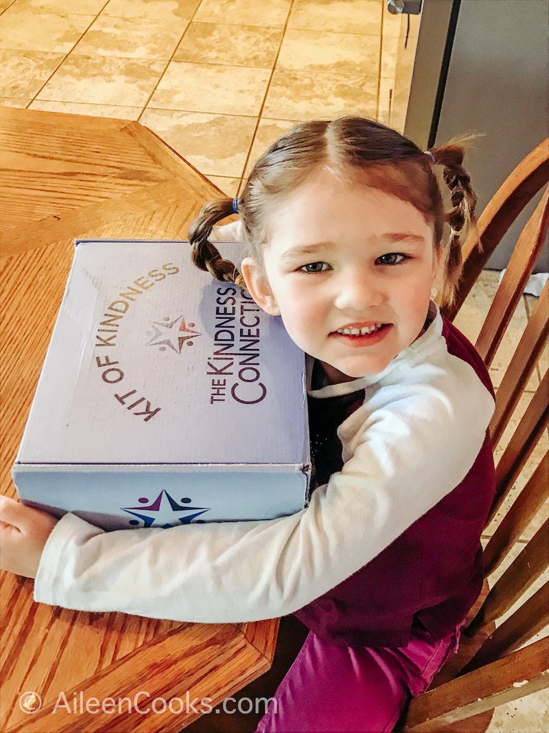A little girl holding a blue box that says kindness connection.
